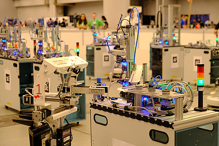 Several machines and the winning robot of Team GRIPS at work