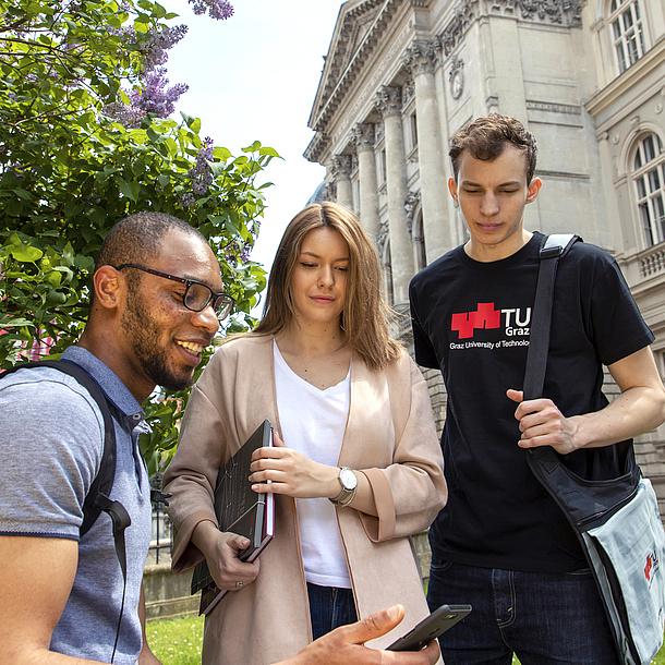 3 Studierende stehen vor der alten Technik und blicken auf ein Smartphone.