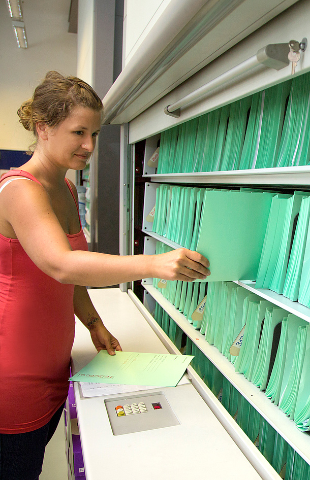 Eine Mitarbeiterin der TU Graz vor den Studienunterlagen der Studierenden, Bildquelle: Lunghammer – TU Graz