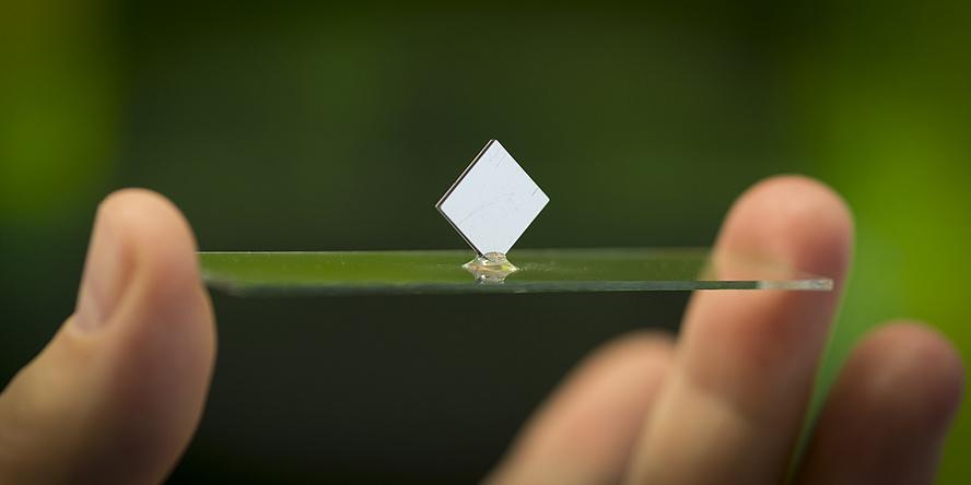 Zwei Finger halten eine Glasplatte auf der ein weißes Quadrat balanciert.