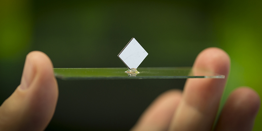 Two fingers are holding a glass plate with a white square standing on it.