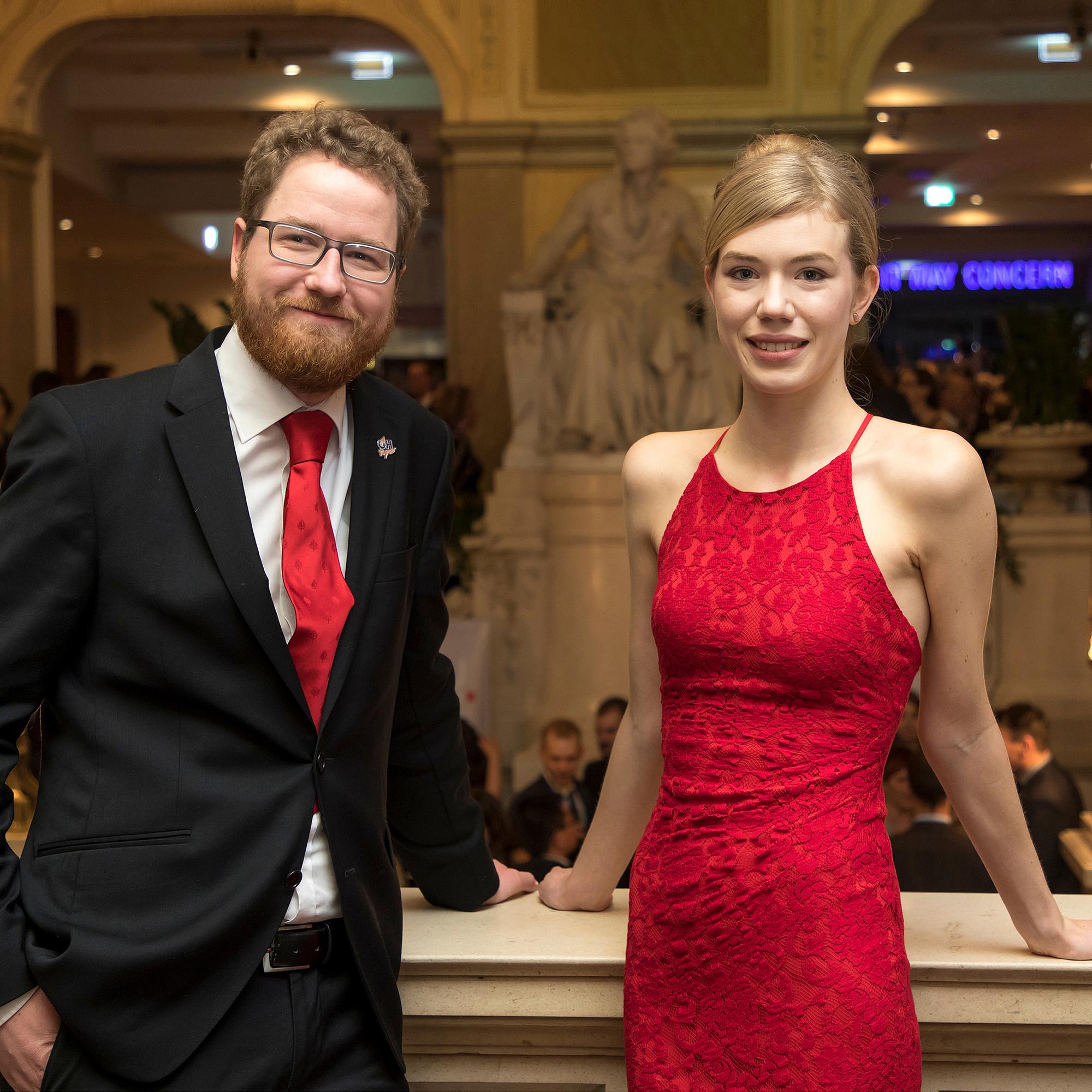 Junger Mann und junge Frau in festlicher Kleidung.