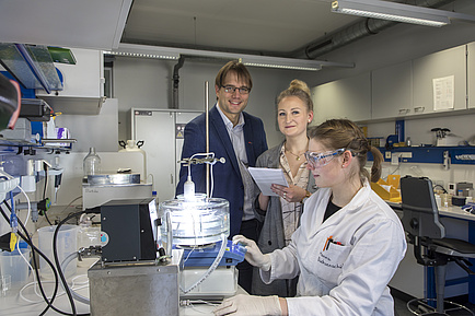 A woman in the lab coat sits in front of a brightly lit apparatus, next to her there is a man and another woman, both of whom look into the camera.
