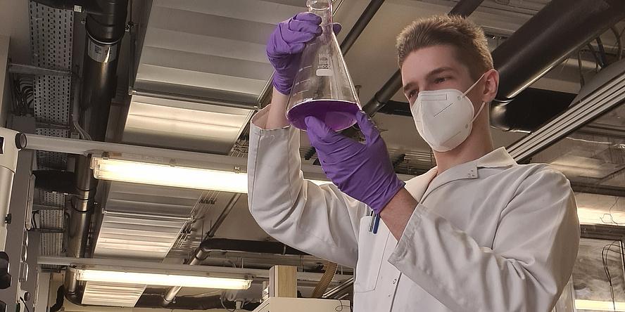 Junger Mann mit weißem Kittel und Maske im Labor