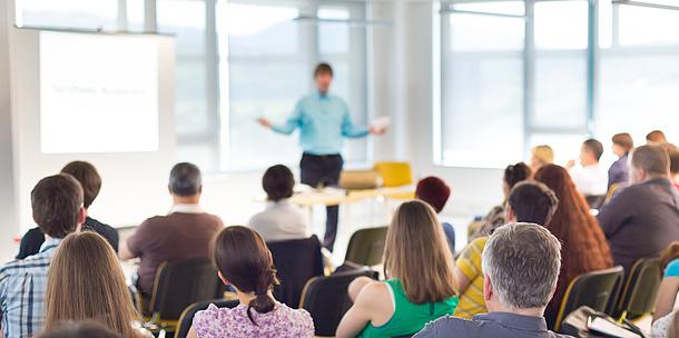 Ein Vortragender steht vor einer Gruppe Personen, die auf Sesseln sitzen. Bildquelle: kasto – Fotolia.com