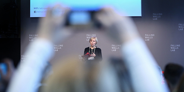 "A woman holds moderation cards in her hand and speaks in front of a wall, on which several times the words ""Falling Walls Lab"" can be seen. Blurred audience can be seen in the foreground."