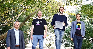 Four white men stand in front of trees, smiling. One is holding a gift box.