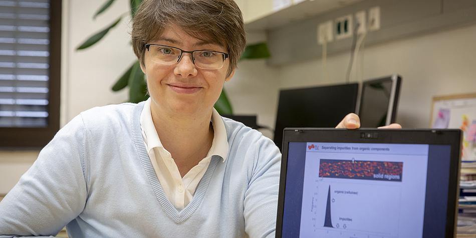 Eine Frau steht neben einem Computerbildschirm