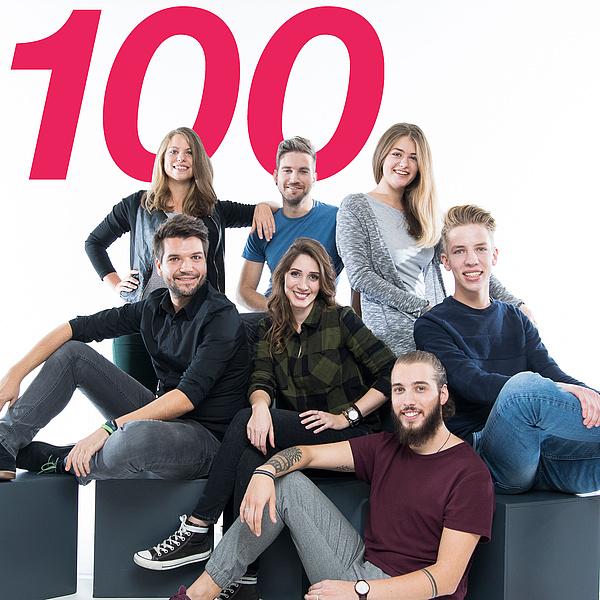 Sieben junge Menschen sitzen zusammen und lachen, Zahl 100 im Hintergrund.