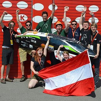 Jubelnde Studierende mit einem Leichtbaufahrzeug und Österreich-Fahne