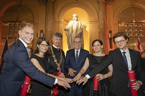 Zwei Frauen und vier Männer stehen im Halbkreis nebeneinander und halten ihre teilweise beringten Hände in die Mitte.