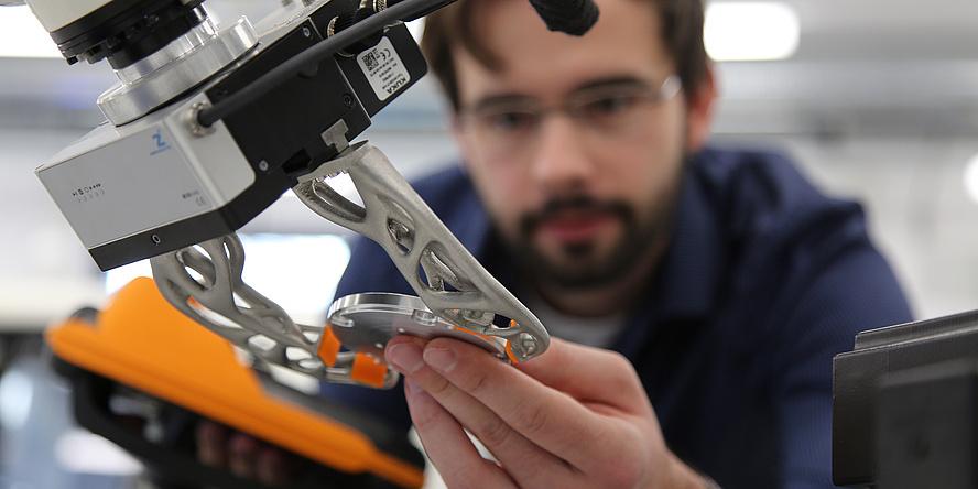 Verschwommen ist ein junger Mann mit Bart zu sehen. Er hält eine metallene Scheibe in der Hand. Ein silberner Roboterarm greift nach der Scheibe.