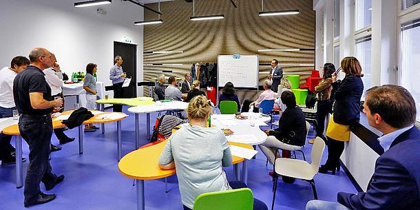 Mehrere Personen stehen und sitzen in einem Seminarraum. Im Hintergrund steht ein Mann an einem Whiteboard.