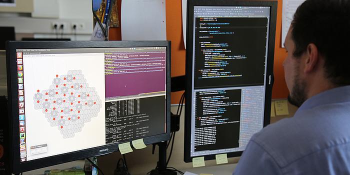 Ein junger Mann schaut auf einen Computerbildschirm. Er hat kurze braune Haare und trägt ein blaues Hemd. Am Bildschirm ist eine graue Grafik mit roten Elementen zu sehen.
