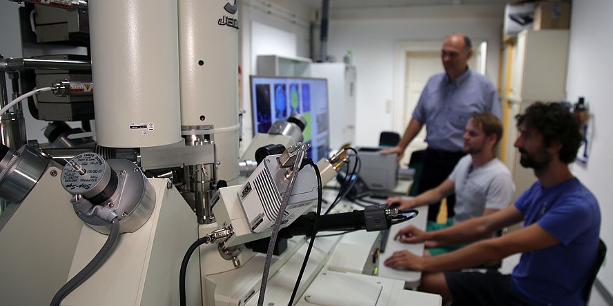 Ein Raum, in dem ein weißtes Gerät mit vielen Röhren steht. Im Hintergrund sitzen drei Männer an einem Schreibtisch. Vor ihnen ist ein großer Computerbildschirm mit vielen bunten Flächen.