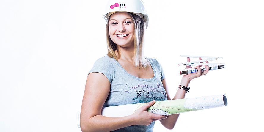 Studentin der TU Graz mit weißem Helm, einer Zeichenrolle unter dem Arm und einem Handwerker-Maßstab in der Hand.