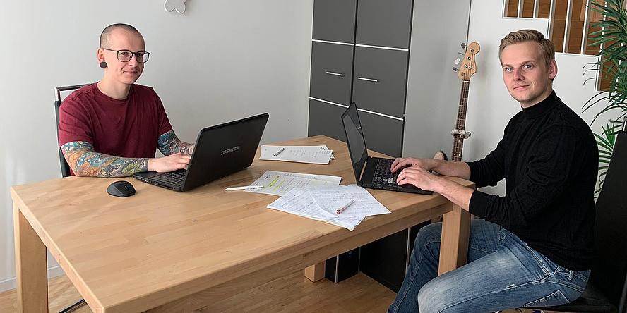 Zwei junge Männer mit Arbeitsunterlagen und Laptops an einem Holztisch.