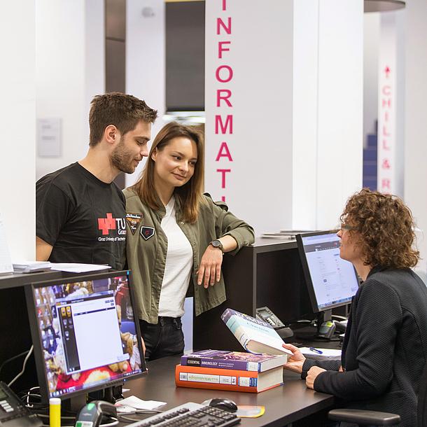 Zwei Studierende stehen an einem Schalter, an dem eine Frau vor einem Computer sitzt.