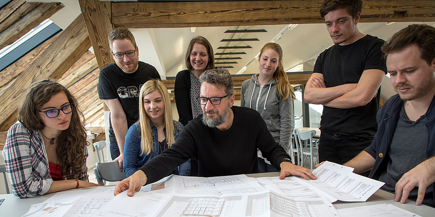 (University assistant Armin Stocker seated at a table with drawings, surrounded by seven students against the background of the renovated roof beam construction in the TU Graz master's studios.