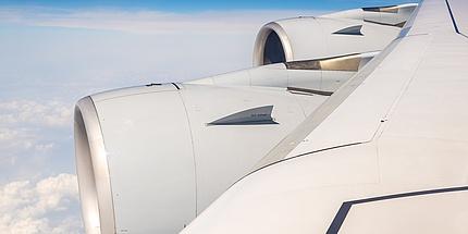 Flügel eines Airbus A380. Im Hintergrund sind Wolken zu sehen.