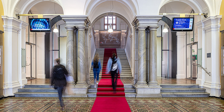Stiegenaufgang mit rotem Teppich in der Eingangshalle eines historischen Universitätsgebäudes