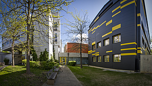 Two modern buildings, one white, the other black with yellow details.