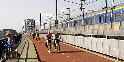 Sommerlich gekleidete Fahrradfahrende am städtischen Fahrradweg parallel zur vorbeifahrenden S-Bahn auf einer Eisenbahnbrücke.