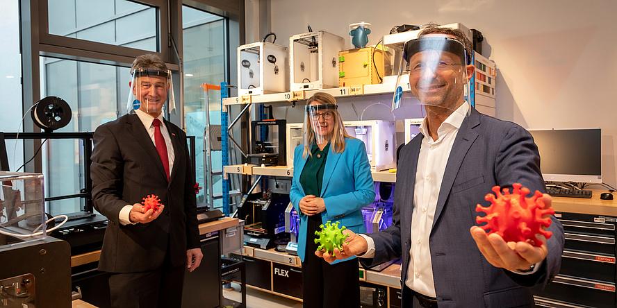 Eine Frau im türkisen Blazer und zwei Herren im Aanzug vor einer Galerie von 3D Druckern im Labor