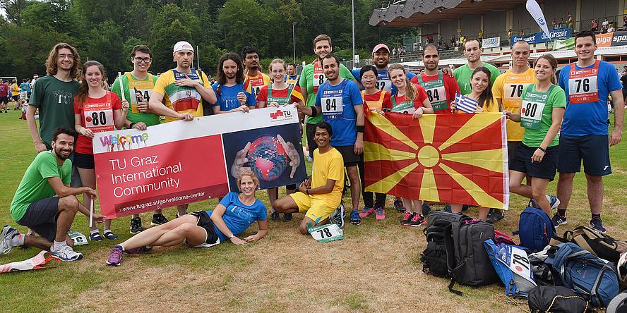 """Das internationale Team der TU Graz in blauen, grünen, gelben und roten Shirts mit Startnummern hält ein Banner mit der Aufschrift """"TU Graz International Community""""."""