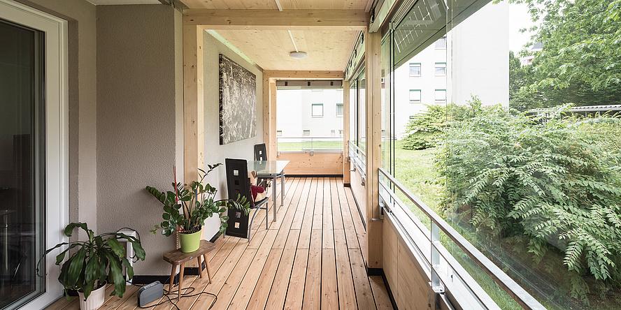 Ein heller, hölzerner Raum mit einer großen Glasfront zum Garten hin.