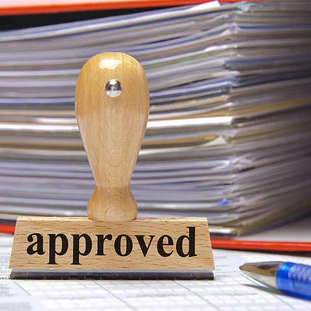 "Stamp labelled ""approved"", behind it a stack of paper. Photo source: Wolfilser - Fotolia.com"