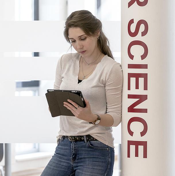 """Junge Frau mit Tablet lehnt an einer Säule mit dem Schriftzug """"Science""""."""
