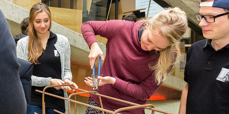 Junge blondhaarige Frau im beerenroten Pulli zwickt Draht ab, der ein Gestell zusammenhält. Eine junge Frau und ein junger Mann assistieren.