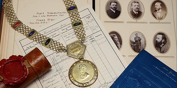 Archivalien: Dokumente, eine Dokumentenrolle und eine Amtskette. Bildquelle: Herbst – TU Graz