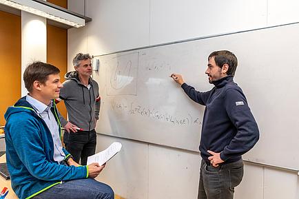 Drei Forscher im Gespräch vor einem Whiteboard