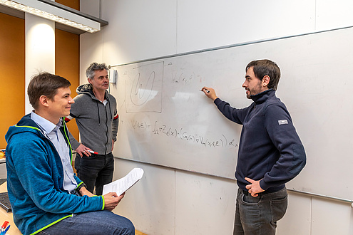 Three researchers in conversation in front of a whiteboard