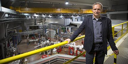 Ein Mann steht vor einem gelben Geländer auf einer Brücke in einem Laborgebäude. Im Hintergrund ist ein weißes rundes Gebäude zu sehen. Rundherum sind viele Kabel.