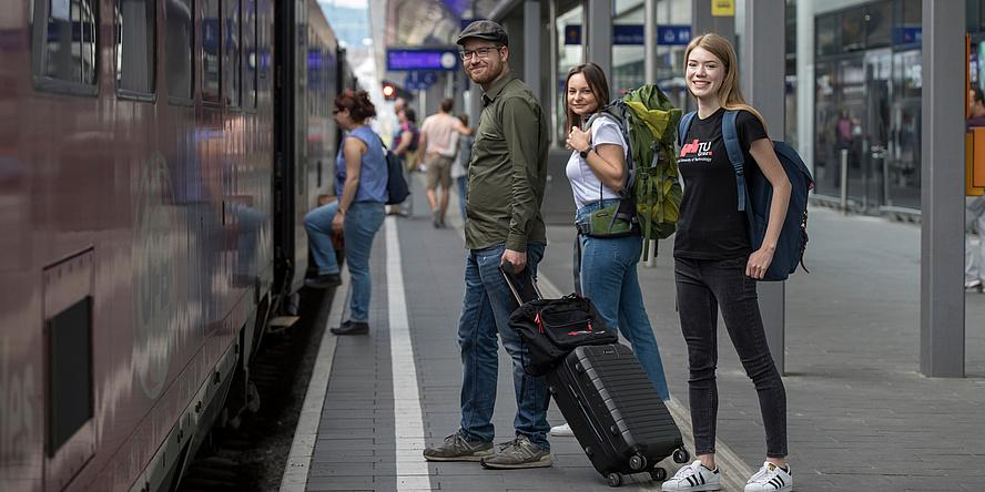Zwei Studentinnen mit Rucksäcken und ein Student mit Koffer am Bahnsteig kurz vor dem Einstieg in einen haltenden Zug am Grazer Hauptbahnhof.