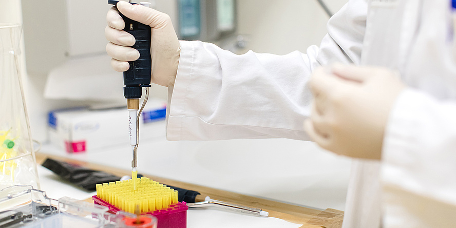 A laboratory situation, a hand with a research pipette docking to a small yellow measuring cylinder. At the table, further laboratory material can be seen, the person wears a white coat.