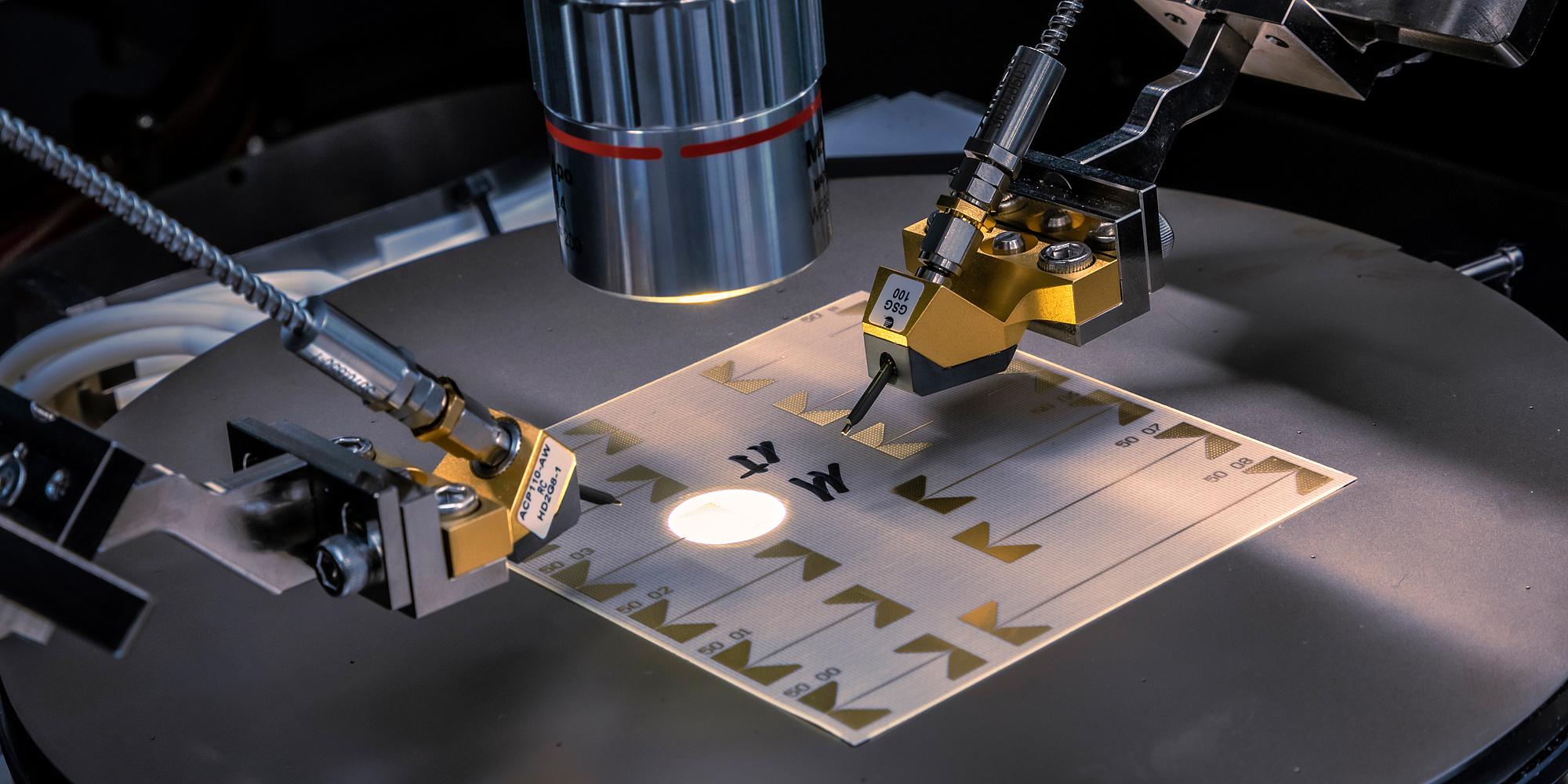 Dünne Folie unter einem Mikroskop wird von zwei feinen Nadeln kontaktiert.