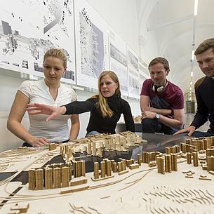 Frauen und Männer stehen an einem Tisch mit Architektur-Modellen.