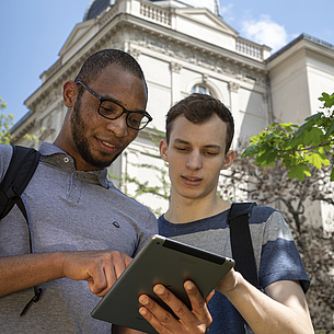Two young men with a tablet in front of a building.