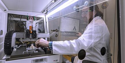 Der Biodrucker ist im Vordergrund. Er druckt eine Struktur aus. Dahinter sitzts Rupert Kargl.
