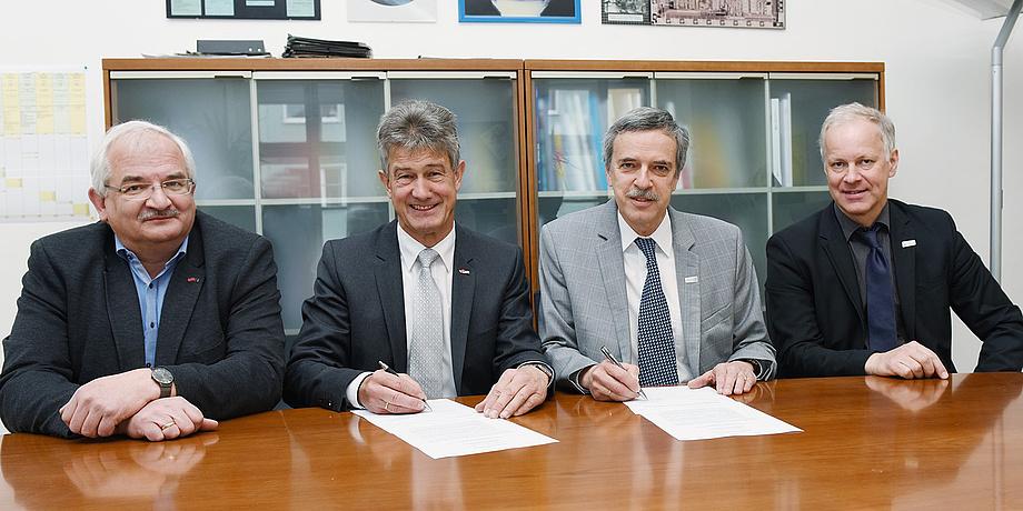 Vier Herren bei der Vertragsunterzeichnung an einem Tisch sitzend