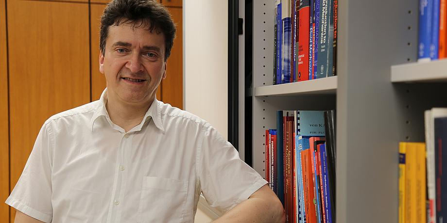 Ein Mann im weißen Hemd lehnt an einem Bücherregal mit vielen bunten Büchern.