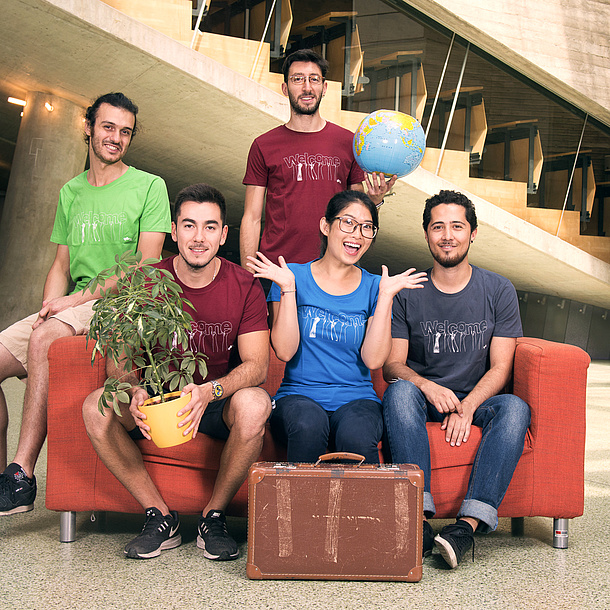 Fünf junge Menschen mit Globus, Topfpflanze und Koffer.