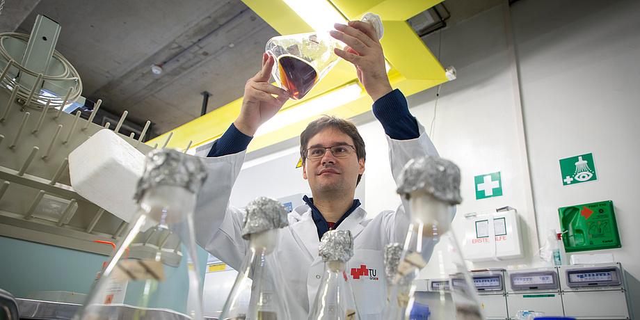 Mann in Labormantel mit Glaskolben
