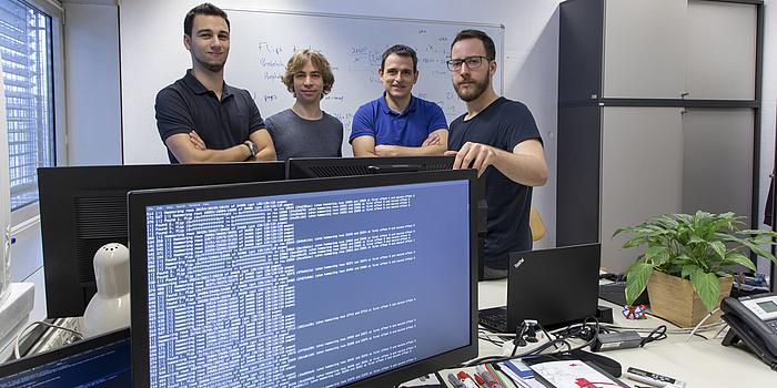 Vier Männer stehen hinter einem Computerbildschirm. Der Computerbildschirm ist blau und hat weiße Schrift.