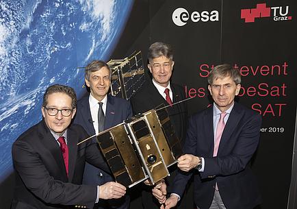 Vier Männer und das Modell des Nanosatelliten