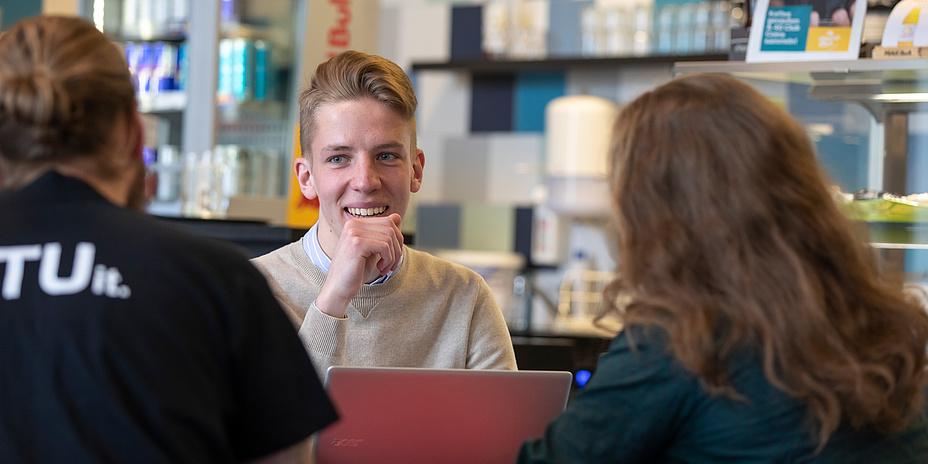 Junger, blonder Mann sitzt mit einem Laptop gemeinsam mit einem Mann und einer Frau, die von hinten zu sehen sind, an einem Tisch. Im Hintergrund Regale mit Dosen und anderem.